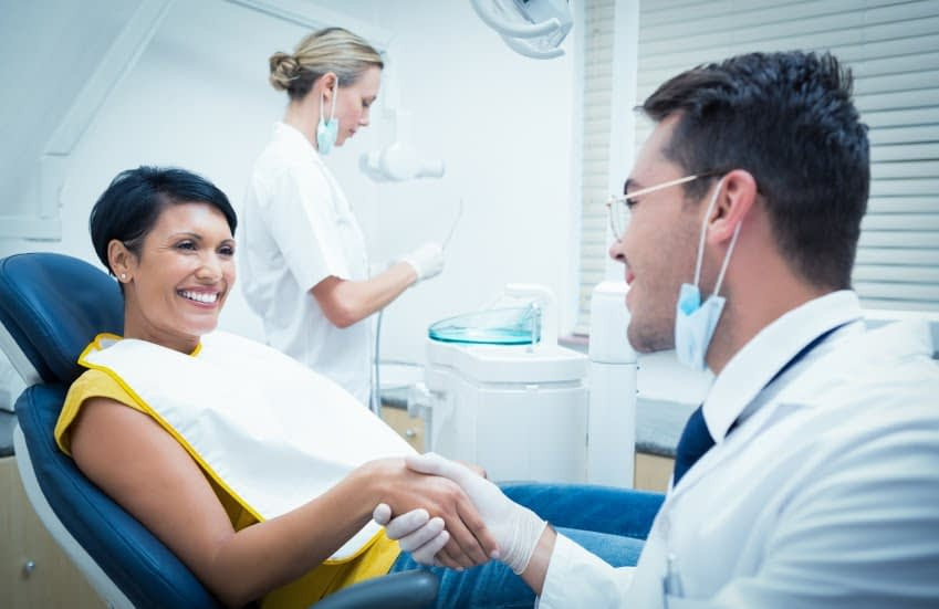 Female patient shaking hands with dentist