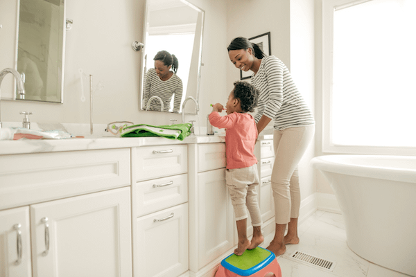 mother with daughter teaching good oral habits and teeth brushing