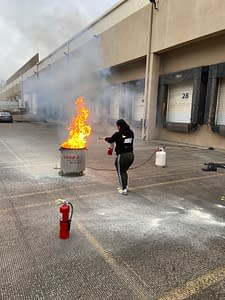 Woman praciticing fire extinguisher saftey during Code 3 Safety & Training class