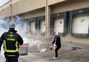Woman using Fire Extinguisher during Code 3 Safety & Training class