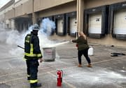 Female practicing the use of Fire Extinguisher safety during Code 3 Safety & Training Course.