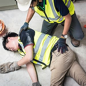 Worker helping injured coworker at construction site