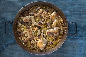 Spanish quail and porcini mushroom rice with artichokes served in large at Boqueria Spanish restaurant in NYC and DC.