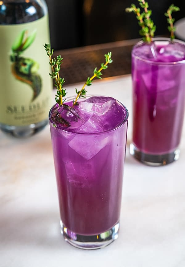 A bright purple cocktail in a tall glass made with Seedlip 'Garden' honey syrup and is purple from pea flowers and pea flower tea.