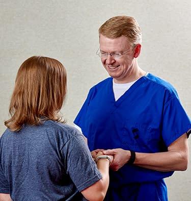 Dr. Carey Clark III treating a hand injury.