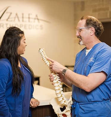 Orthopedic doctors discussing potential spinal problems at Azalea Orthopedics in East Texas.