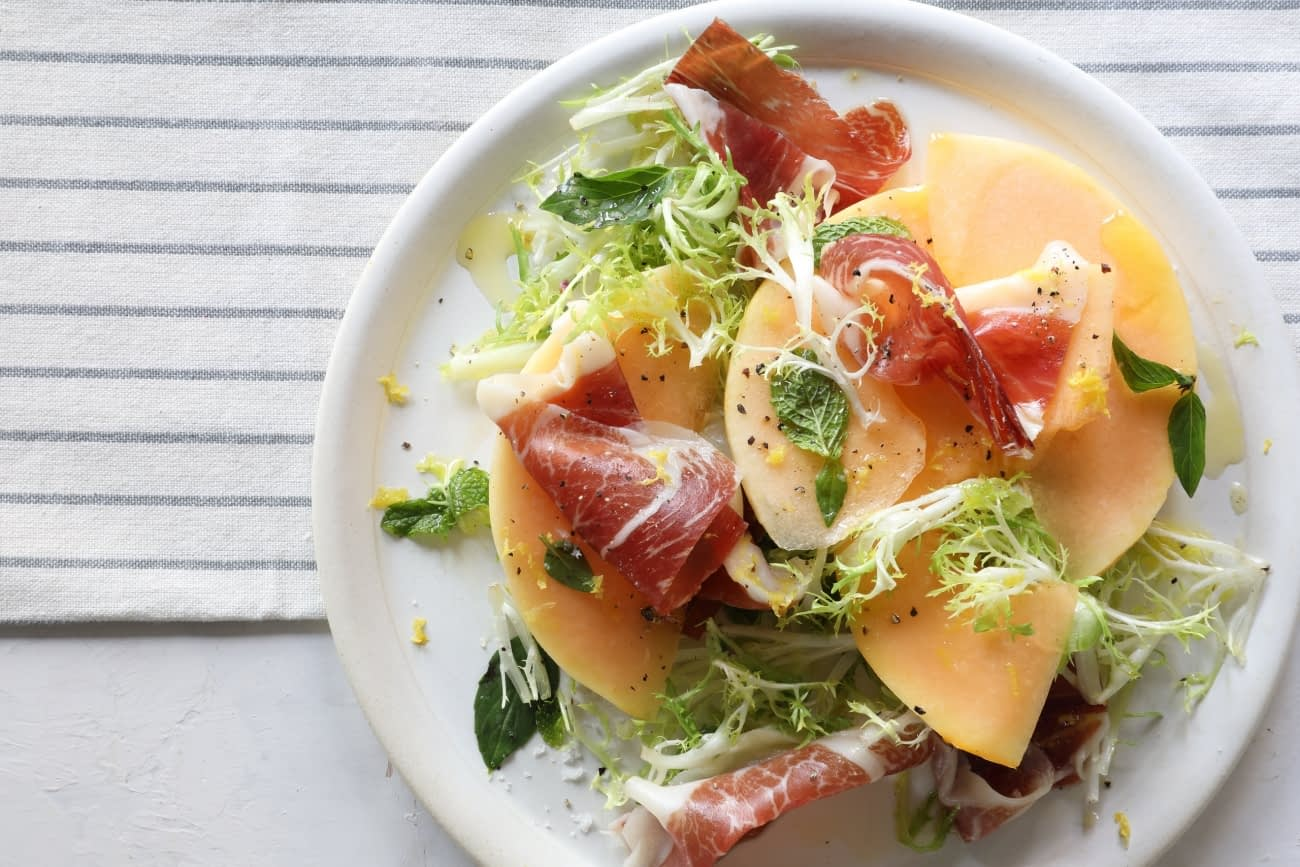 Melon con Jamon on a white plate: Melon with Iberian Ham and Fresh Herbs