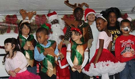 kids of various ages wearing Christmas costumes in a group photo