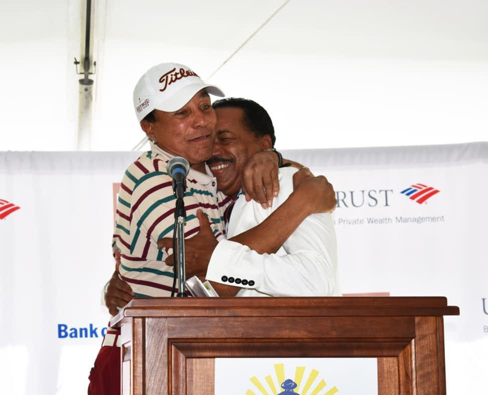 two people hugging at a golf event